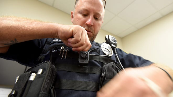 Shelby police officer Keith Swisher mounts his body camera on his vest.
