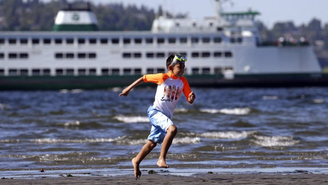 Arian Medina, 7, races along a beach and in view of the Washington state ferry Kitsap on a warm and sunny, Monday, June 8, 2015, in Seattle.