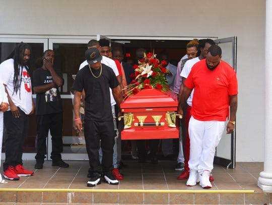 Pallbearers carry out the the bright red casket. Hundreds