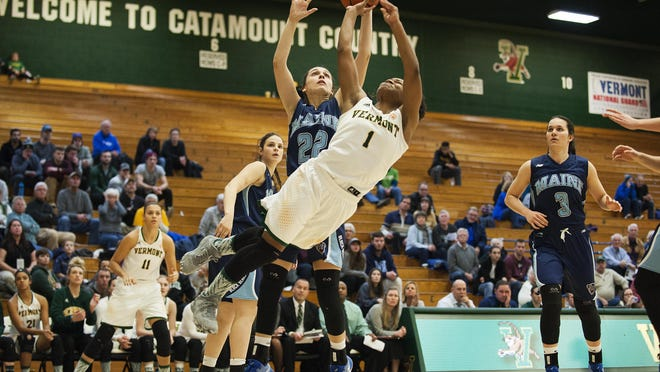 Vermont's Kylie Butler (1) leaps past Maine's Tanesha Sutton (23) for a lay up during the women's basketball game between the Maine Black Bears and the Vermont Catamounts at Patrick Gym on Wednesday night.