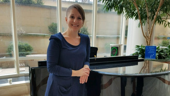 Sioux Falls teacher Katie Blunck poses near a piano at Mayo Clinic in Rochester, Minnesota, where she's receiving treatment for a rare form of brain cancer.