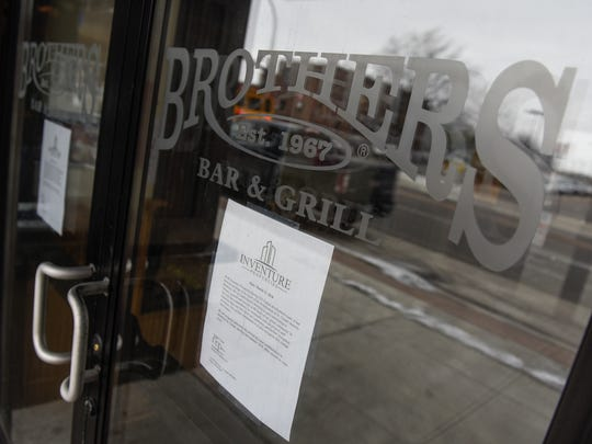 A sign on the door of Brothers Bar & Grill photographed