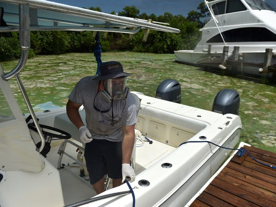 """I'm afraid of the fumes,"" said Austin Kemp, of Central Marine, wearing a gas mask while taking a boat out for a test run in the algae-filled waterway of the St. Lucie River on Thursday, June 30, 2016, in Stuart, after Senator Bill Nelson viewed the algae in the lagoon from their marina."
