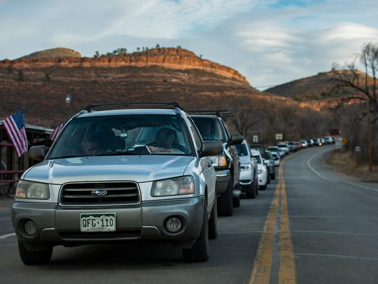 Vehicles wait to be let up Highway 34 at the Dam Store,
