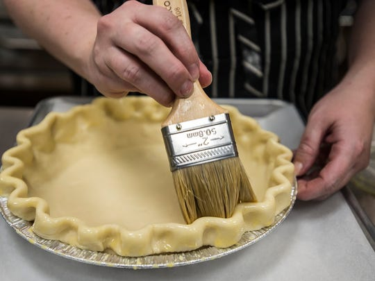 Baker Sharon Phillips glazes the edge of pie crusts with egg wash on Friday, Nov. 17, 2017, at Ginger And Baker in Fort Collins, Colo.