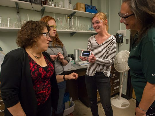 Forth-year chemistry graduate student Tara Van Surksum shows Colorado State University chemistry professor Ellen Fisher, left, CSU professor and Department of Mechanical Engineering head Susan James, right, and fifth-year graduate student Michelle Mann a recent mixed-gas plasma reaction she had made on Nov. 17 at the Chemistry Building on the CSU campus in Fort Collins.