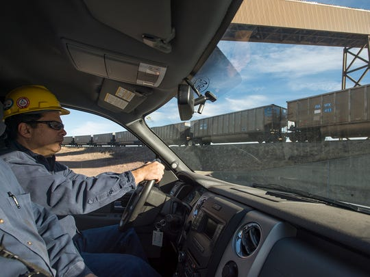 Plant manager Andy Cofas drives under a train delivering coal while leading a tour of the power plant on Tuesday, Nov. 14, 2017, at the Rawhide Energy Station north of Wellington, Colo.