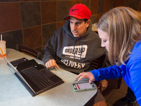 Local OrderUp franchise owner Jeff Marcus and independent subcontract driver Angie Self look at dispatch calls before Self takes a food delivery on Wednesday, Nov. 29, 2017, in Fort Collins, Colo.