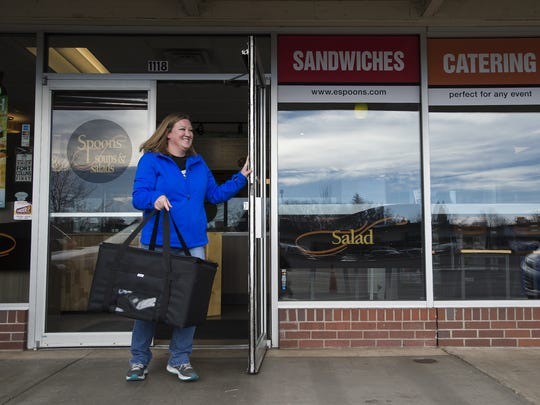 Order Up independent subcontract driver Angie Self takes a food delivery from Spoons Soups and Salads on Wednesday, Nov. 29, 2017, at in Fort Collins, Colo.