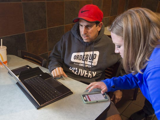 Local Order Up franchise owner Jeff Marcus and independent subcontract driver Angie Self look at dispatch calls before Self takes a food delivery on Wednesday, Nov. 29, 2017, at in Fort Collins, Colo.