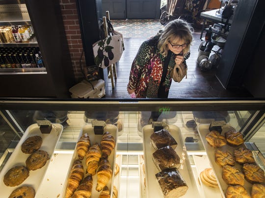 First-time customer Laurie Koralewski looks over a selection of baked goods on Friday, Nov. 17, 2017, at Ginger And Baker in Fort Collins, Colo.