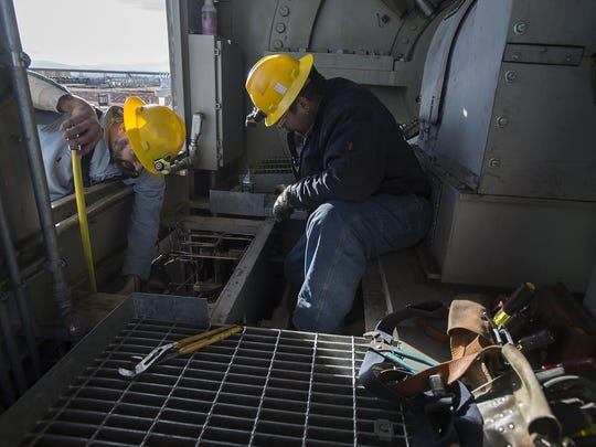 Technicians Anthony Belmore, left, and Joe Kroll work on one of the plant's combustion turbines on Tuesday, Nov. 14, 2017, at the Rawhide Energy Station in Wellington, Colo.