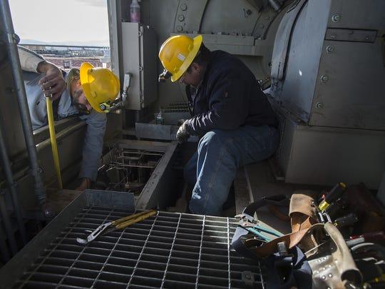 Technicians Anthony Belmore, left, and Joe Kroll work