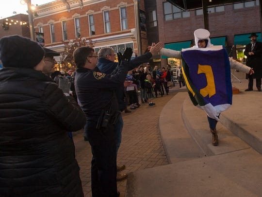 Denise Negrete gives a high five to Fort Collins mayor Wade Troxell while wearing a dreidel outfit during a Menorah Lighting & Chanukah Celebration on Sunday, Dec. 17, 2017, in Old Town Square in Fort Collins, Colo.