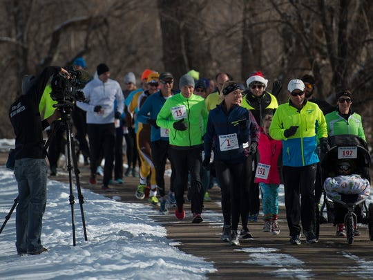 Kevin Follett leads a group of runners along the Poudre River Trail in Laporte on Saturday while running his 100,000th mile with family and friends.