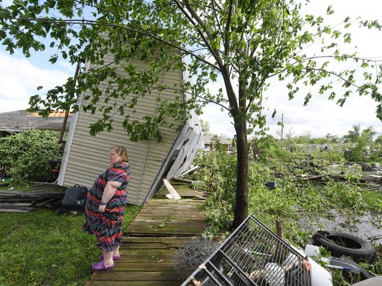 Angel Funk stands in the backyard of her Franklin, Texas, home following severe weather, Saturday. Funk's home was struck by her neighbor's mobile home, but she and her husband, who were home at the time, escaped unharmed.