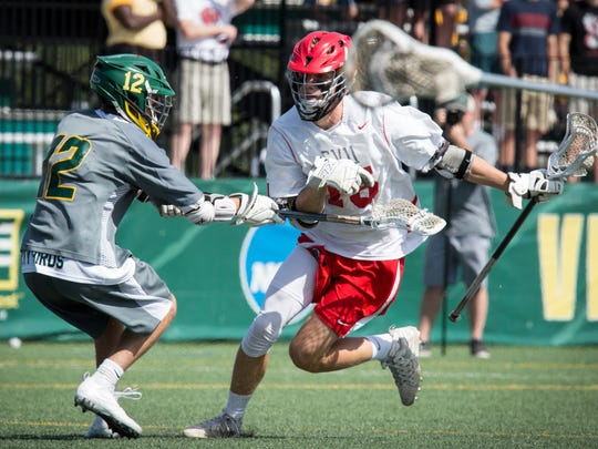CVU's Sam Sturim carries the ball during Saturday's Division I boys lacrosse final. Mac Kennedy of BFA defends.