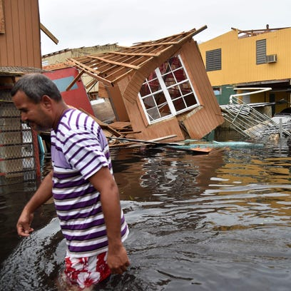 A man walks past a house laying in flood water in Catano