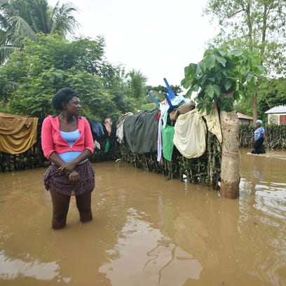 Marie Charlotte walks through water near her house