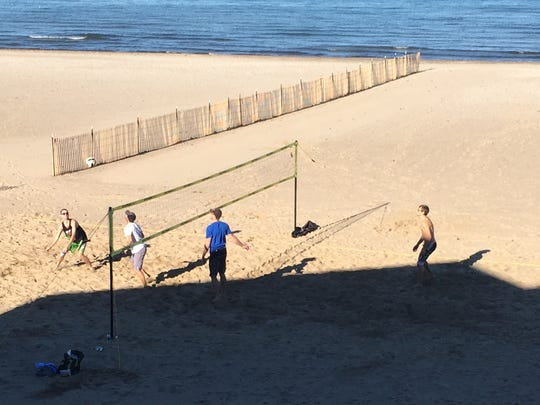 A group of young men celebrate record-high temperatures by playing volleyball at Ontario Beach State Park on Wednesday.
