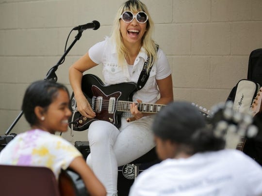 Carley Wolf of the Ghost Wolves shares a laugh with sisters (from left) Reena and Soundarya Ritzman of Appleton as she gives a guitar lesson Saturday at Heid Music during Mile of Music.