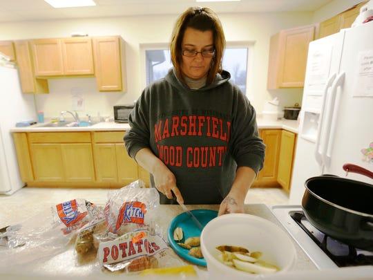 Shauna Weinfurtner cuts potatoes while making dinner