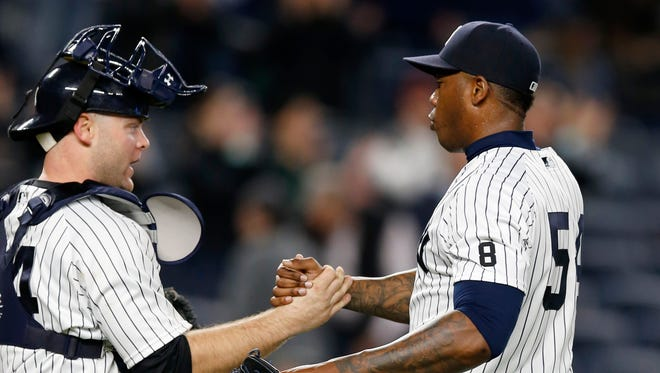 New York Yankees catcher Brian McCann, left, congratulates New York Yankees relief pitcher Aroldis Chapman (54) after Chapman closed out the Yankees 10-7 victory over the Kansas City Royals in a baseball game at Yankee Stadium in New York, Tuesday, May 10, 2016.