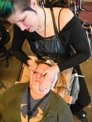 Iowa School of Beauty's Meagan Tron gives Scavo counselor Carmen Rasmussen a massage on March 4, 2017, during Spring Community Night at Scavo High School.