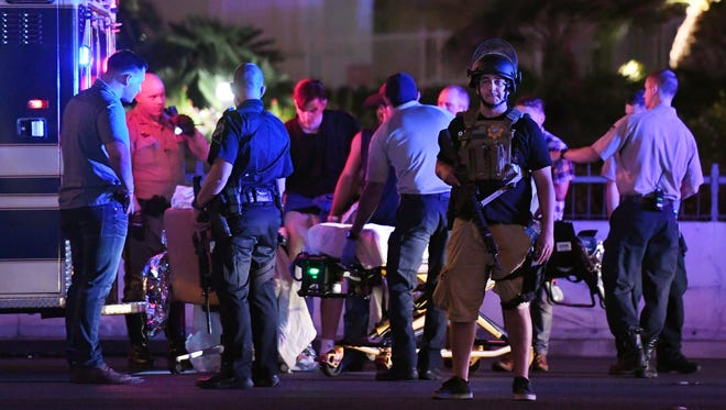 Police officers stand by as medical personnel tend to a person on Tropicana Avenue near Las Vegas Boulevard after a mass shooting Oct. 1, 2017, at a nearby country-music festival.