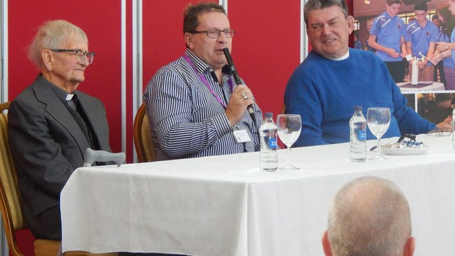 """Canon """"Kerry"""" Waterstone, left, founder of the Ulster Project, listens during a presentation at the 2015 Ulster Project International Conference about the project in Hutchinson, which  annually hosts teens from Portadown, Northern Ireland. Speaking is Keith Neill, who is now a youth minister in Hutchinson, and to his right is the Rev. Steve Jacobson, a U.S minister  who helped start the first project. Neill, a teen that first year in 1975, was a counselor for the project for many years in Hutchinson before moving here."""