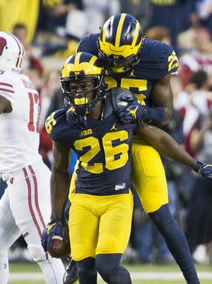 Michigan cornerback Jourdan Lewis (26) celebrates his interception of a pass with teammate safety Dymonte Thomas in the Oct. 1 win over Wisconsin.