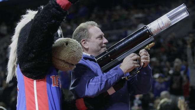 Michigan State basketball coach Tom Izzo, right, shoots T-shirts into the stands with the help of Hooper at the Palace of Auburn Hills on April 8, 2015.