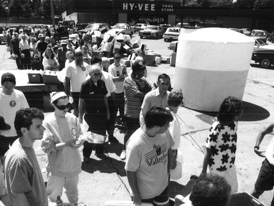 A crowd faces a two-hour wait for water at the Hy-Vee store at 27th Street and Ingersoll Avenue on Monday, July 12, 1993, around noon. The jugs were being filled with a garden hose, bottom right.