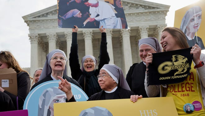 Nuns with the Little Sisters of The Poor, including Sister Celestine, left, and Sister Jeanne Veronique, center, rally outside the Supreme Court in Washington, Wednesday, as the court hears arguments to allow birth control in health care plans in the Zubik vs. Burwell case.