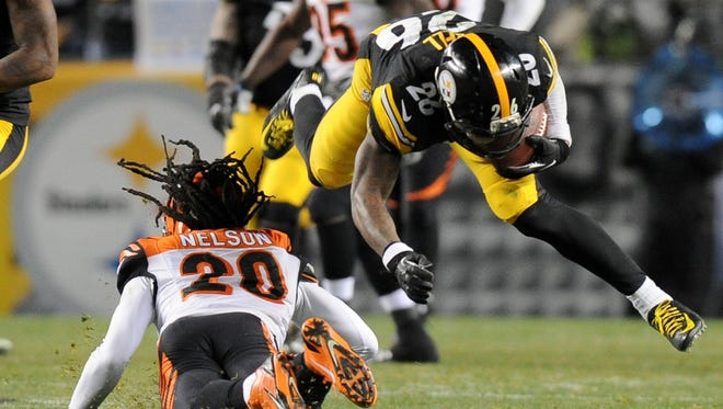Pittsburgh Steelers running back Le'Veon Bell, right, is hit by Cincinnati Bengals safety Reggie Nelson on Dec. 28, 2014, in Pittsburgh.