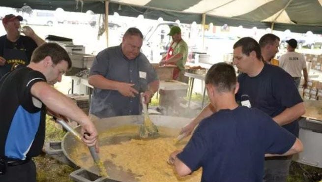 Volunteer workers stir scrambled eggs with ham and cheese in a giant frying pan during Brown County Breakfast on the Farm at Wayside Dairy LLC in 2013.