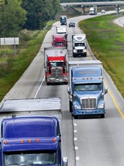 Tractor-trailers and passenger cars share the roadway.