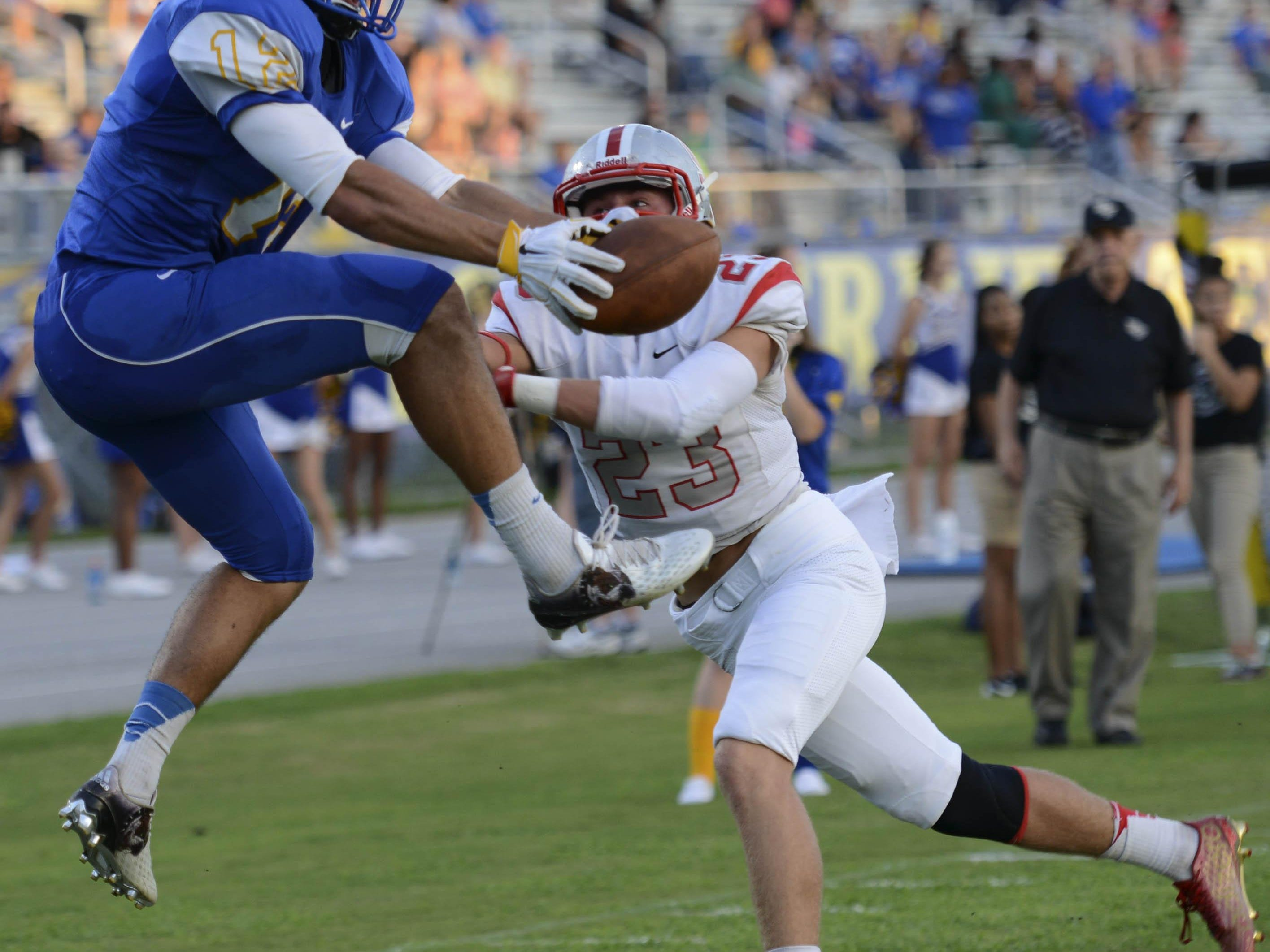 Titusville's Tommy Mack goes over Satellite's Caden Larkin (23) to make the TD catch during Friday's game in Titusville.