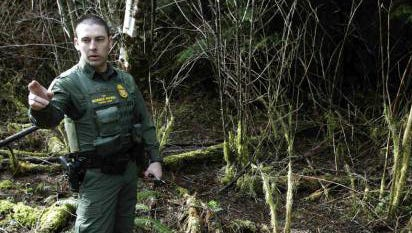 U.S. Border Patrol Agent Chris Dyer stands in a forested area near Forks, Wash., in March 2011.
