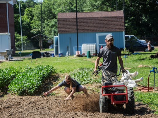 Becca Hart, community garden organizer, and Chris Peterson, farm manager, work Thursday at the urban farm on Ball Road.