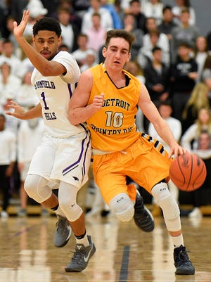 It's a meeting of the guards as Bloomfield Hills senior Justin Henry (1) slides up court with Country Day's senior captain Paul Mocur (10).