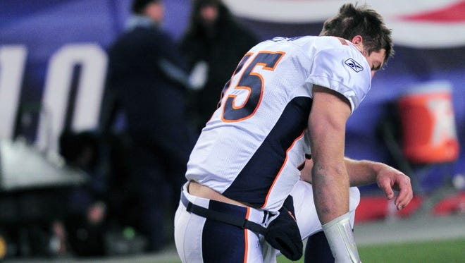 This file photo from 2012 shows Broncos quarterback Tim Tebow kneeling before an AFC playoff game against Patriots at Gillette Stadium in Foxborough, Mass.