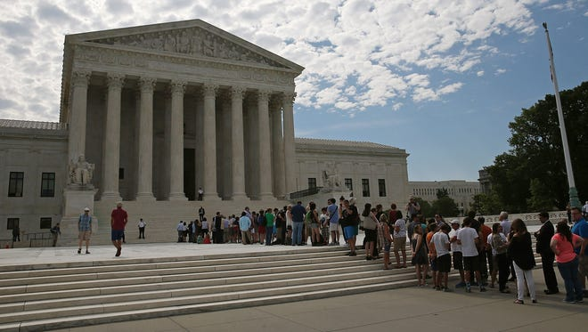 People wait in line to enter the U.S. Supreme Court on June 22, 2015 in Washington.