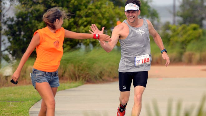A triathlete gets words of encouragement during last year's Pensacola Triathlon. This year's event gets underway at 6:15 a.m. Sunday, April 29, at Community Maritime Park.