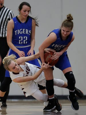 Fox Valley Lutheran High School's Cassidy Duciaume, bottom left, battles for a loose ball against Wrightstown High School's Meghan Riha, righ, during their girls basketball game Thursday, January 18, 2018, in Appleton, Wis. 
