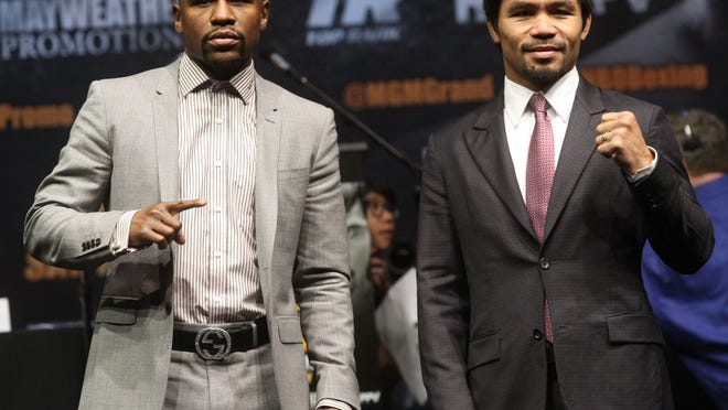Floyd Mayweather Jr. and Manny Pacquiao pose for photographs at their end of their press conference at the Nokia Theater in Los Angeles, California on March 11, 2015.