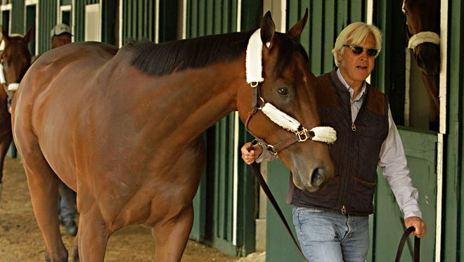Kentucky Derby winner American Pharoah is held by trainer Bob Baffert at the stakes barn at Pimlico Race Course in Baltimore, Wednesday.