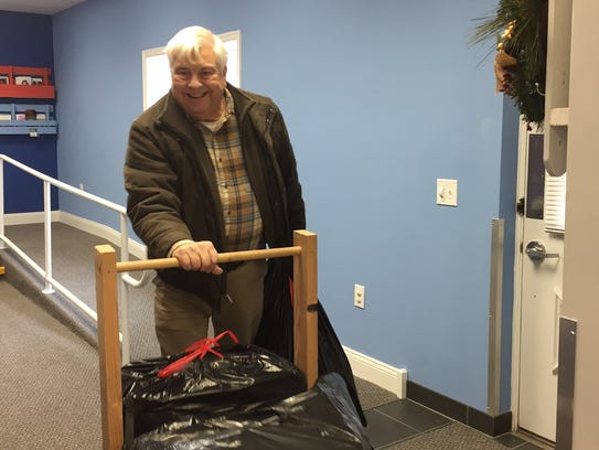 Volunteer Alan Ford brings Holiday Hands gifts into