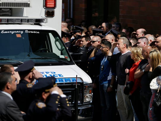Police officers and others salute as the body of Brian Moore leaves Jamaica Hospital in New York May 4. Brian Moore, a 25-year-old police officer shot in the head over the weekend while attempting to stop a man suspected of carrying a handgun, has died from his injuries, the third New York Police Department officer slain in the line-of-duty in five months, a City Hall official said Monday.