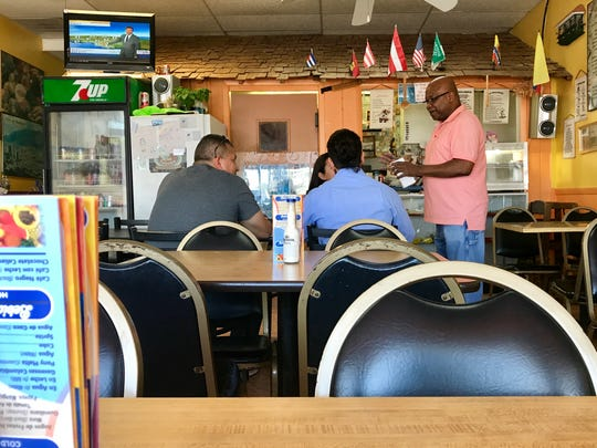 Owner William Mosquera, right, tends to customers at